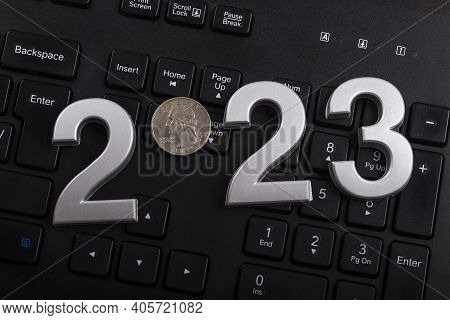 Black Keyboard Close-up. On It Are Laid Out Numbers Of Metal 2023 In The Center Of The Coin 0.25 Dal
