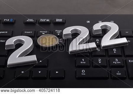 Black Keyboard. Close-up. On It Are Laid Out Numbers Of Metal 2022 In The Center Of The Coin 2 Euro