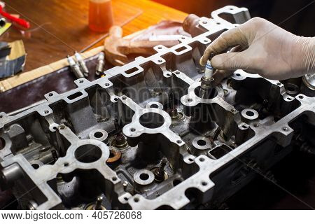 Auto Mechanic Working In Garage. Repair Service.  Opened Automobile Engine Cylinder Head For Mainten