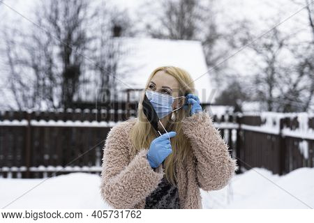 Double Mask. A Young Woman Puts On The First Mask With Her Left Hand Behind Her Ear And Holds The Se