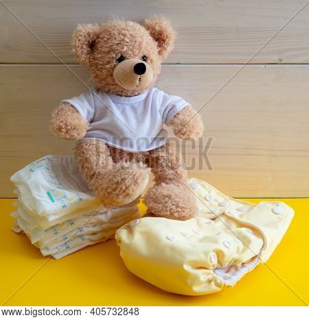 Baby Diaper Choice Concept. Teddy Sitting On Cloth Reusable Nappy And Disposable Diapers