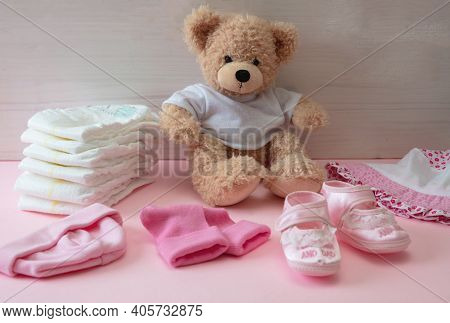 Baby Girl Accessories Diapers And Clothes, Teddy Sitting On Pink Color Floor