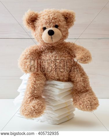 Baby Diapers Stack And Teddy On White Color Floor