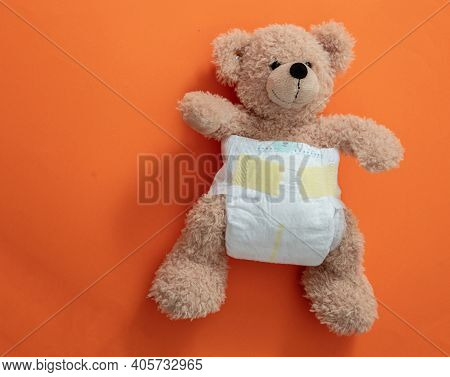 Teddy With A Baby Diaper On Orange Color Background.