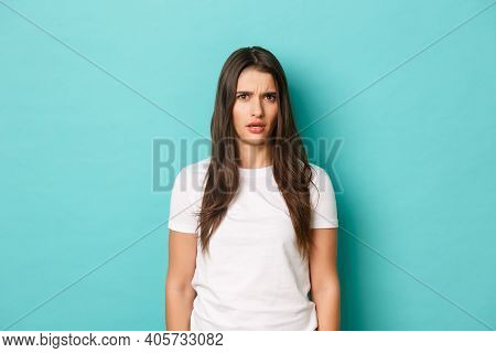 Image Of Confused Brunette Woman In White T-shirt, Frowning And Looking Perplexed At Something Stran