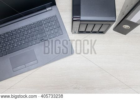 View From Above For Office Workplace With Notebook And Nas Backup Server On A Wooden Background. Bac
