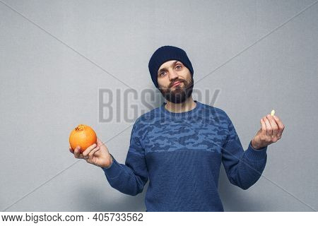A Bearded Guy Holds An Orange And A Suppository For Hemorrhoids In His Hands. Hemorrhoids Concept.