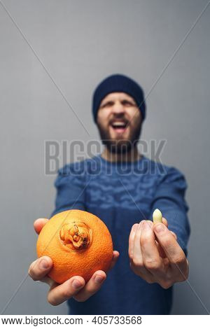 A Man Screams In Problems Due To Hemorrhoids. A Bearded Guy Holds An Orange And A Suppository For He