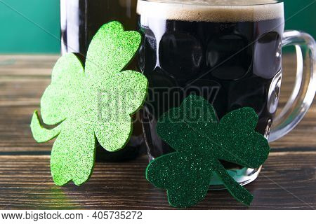 Close-up Of Two Shiny Clover Leaves On A Mug Of Stout. St. Patrick And Stout Concept