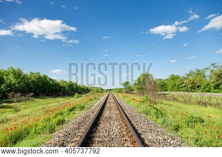 Railroad Stretching Into Distance Against Background Of Blue Sky And White Clouds. Railroad Perspect