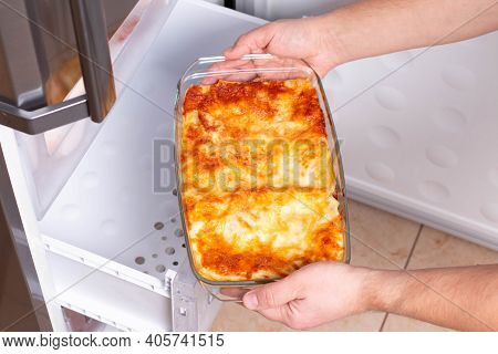 Frozen Ready Meals. Man's Hands Are Taking Frozen Lasagna From The Freezer Of The Fridge. Concept Of
