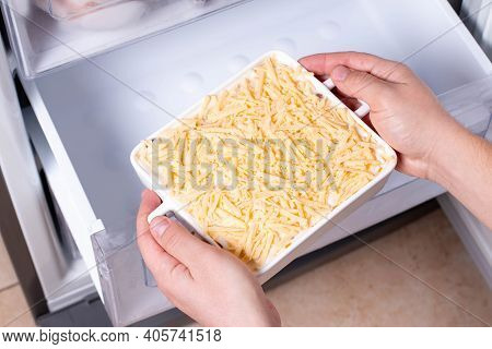 Frozen Ready Meals. Man's Hands Are Taking Frozen Casserole From The Freezer Of The Fridge. Concept