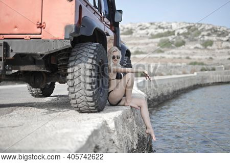 young woman in bikini leaning against an off-road vehicle