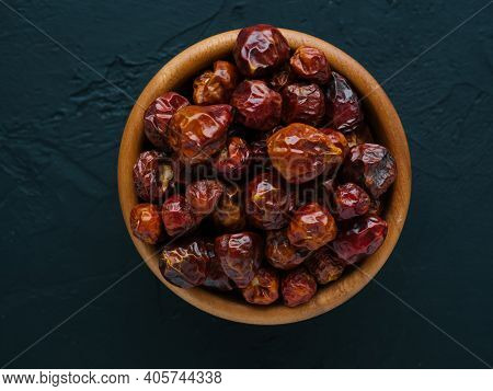 Whole Small Dry Red Hot Pepper On Bowl In Black Stone Background. And Seasonings For Cooking. Dried