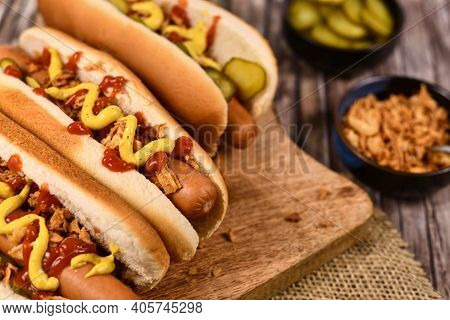 Homemade Hot Dogs With Sausages And Buns Topped With Preserved Pickles, Ried Roast Onions, Mustard A