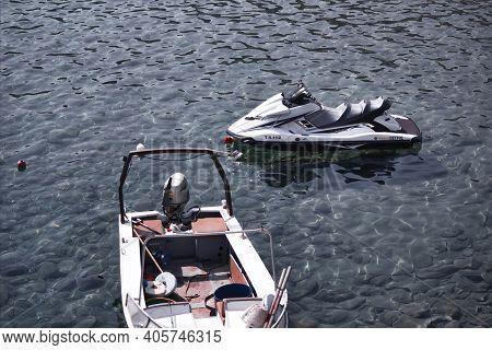 Kreta Or Crete, Greece - September 10, 2017: A Docked Or Parked White Jet Ski And A Motor Boat Float