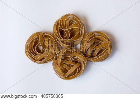 Raw Whole Grain Brown Pasta Tagliatelle On A White Background, Made With Wheat Flour, Rich In Nutrie