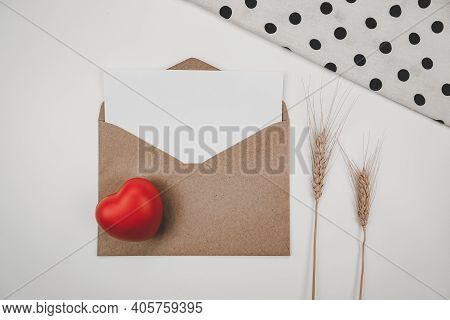 Blank White Paper Is Placed On Open Brown Paper Envelope With Red Heart And Barley Dry Flower And Wh