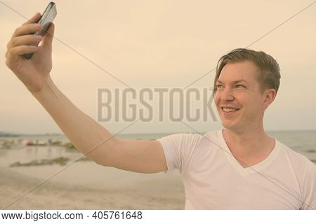 Young Happy Handsome Man Smiling While Taking Selfie Picture With Mobile Phone At The Public Beach O