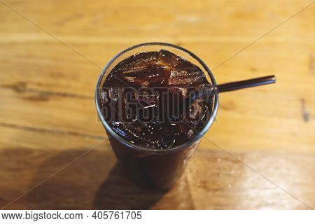 Iced Black Coffee In A Glass Is On A Wooden Table.
