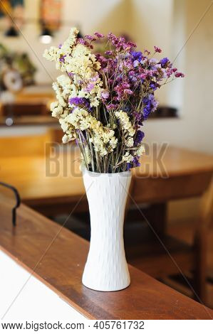 A Bouquet Of Dried Flowers In A Tall White Flower Vase