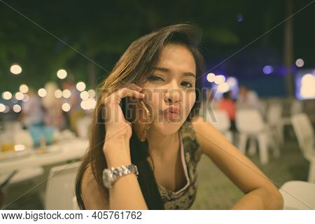Close Up Of Young Beautiful Asian Woman Talking On Mobile Phone While Puckering Her Lips At The Nigh