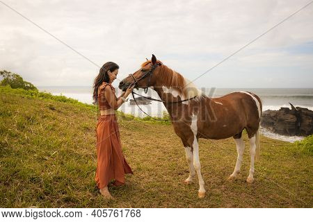Beautiful Woman Leading Horse By Its Reins. Horse Riding. Human And Animals Relationship. Nature Con