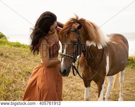 Asian Woman Cuddling Her Horse. Horse Riding. Human And Animals Relationship. Nature Concept. Bali,