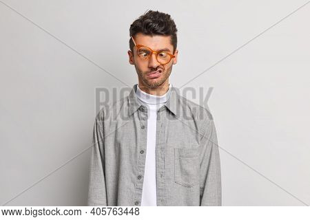 Funny Nerdy European Man Crosses Eyes Makes Grimace Pretends To Be Fool Wears Transparent Spectacles