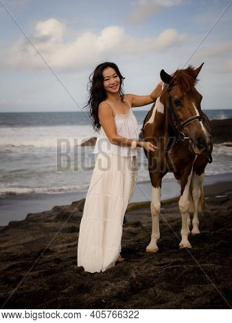 Woman Leading Horse By Its Reins. Horse Riding On The Beach. Human And Animals Relationship. Asian W