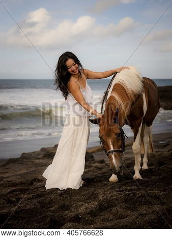 Woman Leading Horse By Its Reins. Horse Riding On The Beach. Love To Animals. Asian Woman Wearing Lo