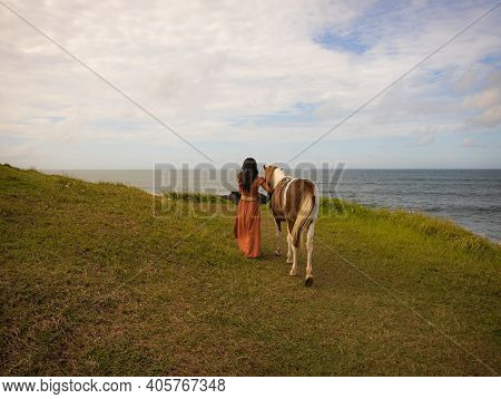 Woman Leading Horse By Its Reins. Horse Riding. Love To Animals. Traveling Concept. View From Back.