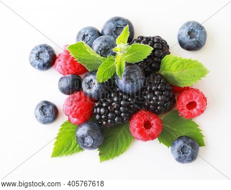 Mix berries with leaf. Various fresh berries isolated on white background. Raspberry, Blueberry, Cranberry, Blackberry and Mint leaves. Close up.