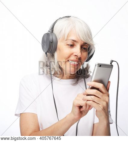 Old people, lifestyle, emotion and technology concept: portrait of happy senior woman with white hair listening to music with headphones over white background