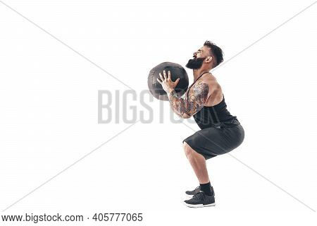 Muscular Tattooed Bearded Male Exercising Fitness Weights Medicine Ball In Studio Isolated On White