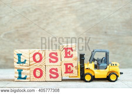 Toy Forklift Hold Letter Block E To Complete Word Lose Lose On Wood Background