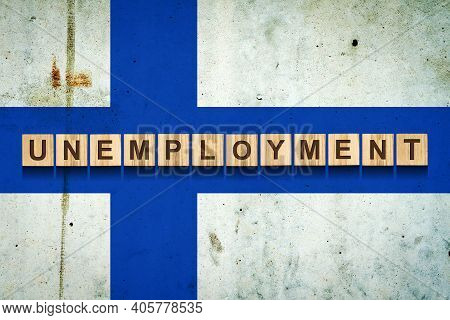 Unemployment. The Inscription On Wooden Blocks On The Background Of The Finland Flag. Unemployment G