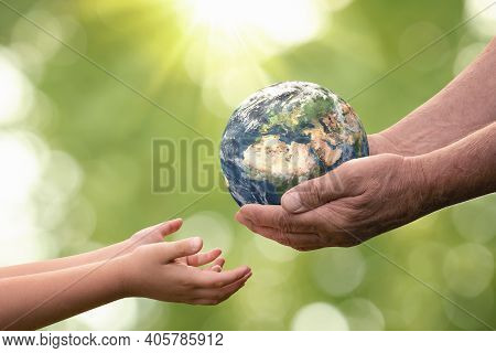 Close Up Of Senior Hands Giving Small Planet Earth To A Child Over Defocused Green Background With C