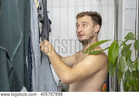 A Man With A Bare Torso On The Balcony Removes Underwear From The Rope. Concept: Bachelor Life, Hous