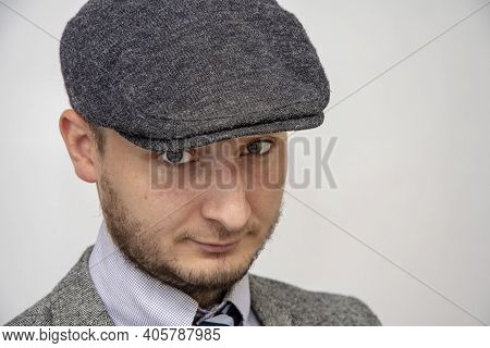 Portrait Of A 35-year-old Man With A Beard In A Suit And Cap On A Gray Background, Close-up, Selecti