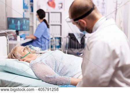 Unhealthy Old Woman With Respiratory Infection Wearing Oxygen Mask In Clinic Infected With Covid19.