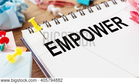 Empower - Text On A Notepad With Wrinkled Paper And Paper Needles On Wooden Background.