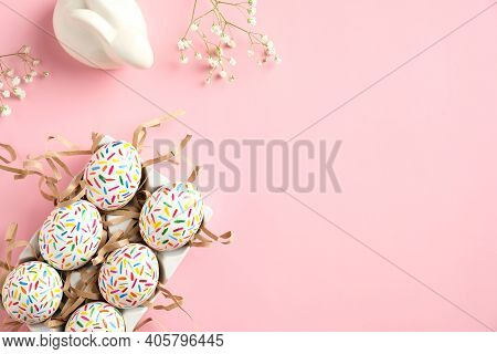 Happy Easter Concept. Cute Easter Eggs, Bunny And Spring Flowers On Pink Table. Flat Lay, Top View,