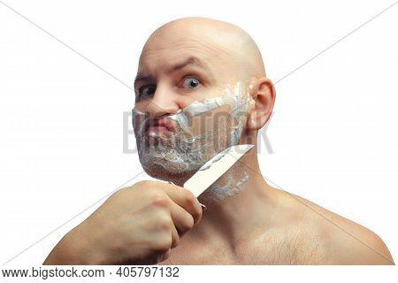A Bald White Man Shaves His Stubble With A Shiny Kitchen Knife. A Mans Face With Shaving Foam. Portr