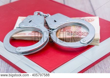 Handcuffs And Money On The Book. Criminal Penalty For Fraud