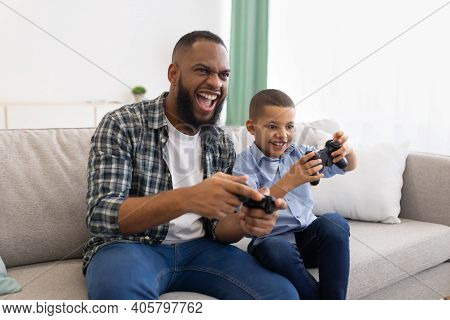 Excited African Dad And Son Playing Game Having Fun Sitting On Couch At Home. Young Black Father And