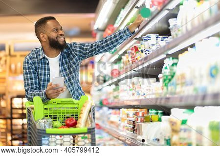 Black Male Buyer Shopping Groceries In Supermarket Taking Dairy Product From Shelf Standing With Sho