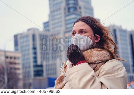 Portrait Of Adult Woman With Curly Hair Wearing Ffp2 Respirator On City Street