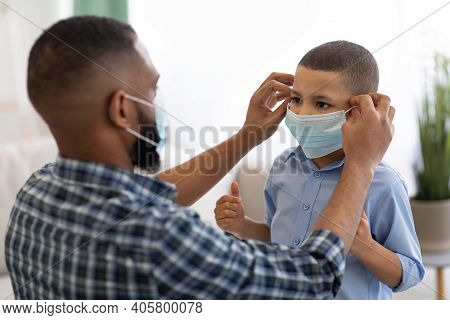 Coronavirus Prevention. Black Dad Putting On Protective Surgical Mask On Sons Face Before Walk Stand
