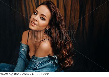 A Brunette With Long Hair Poses In A Studio Sitting On The Floor On A Black Background